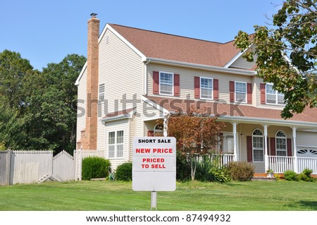 Short Sale Realtor Sign on Two Story Home Front Yard in Suburban Residential Neighborhood Sunny Blue Sky Day