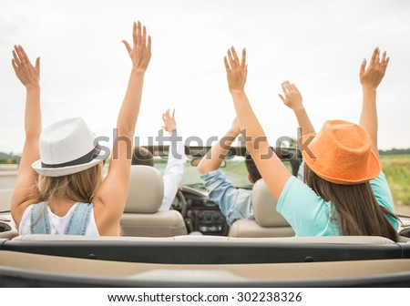 Shot back. Happy friends traveling on the cabriolet with hands up. - stock photo