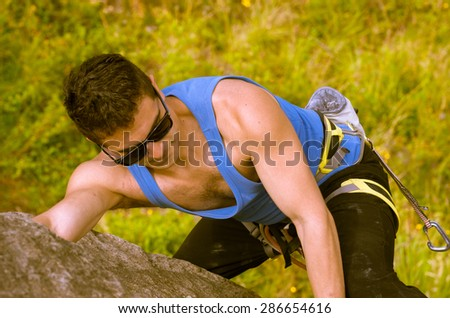 shot from above angle of man climbing mountain with sunglasses - stock photo