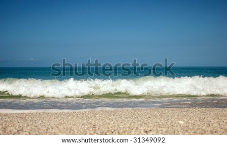 Shot from the ground the ocean waves come crashing towards the viewer below the horizon. Plenty of room for copy. - stock photo