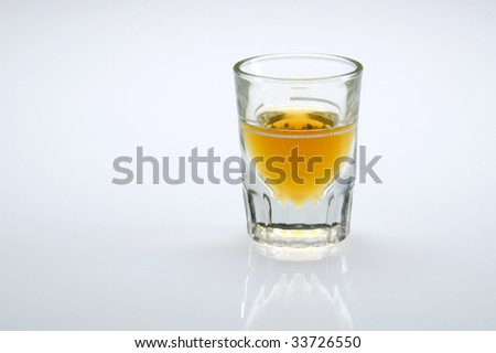 Shot glass filled with whiskey or scotch with reflection.