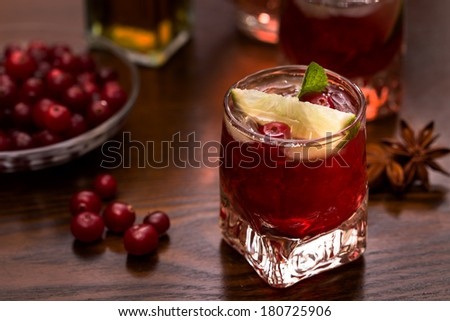 Shot glass of vodka with lime and cranberry - stock photo