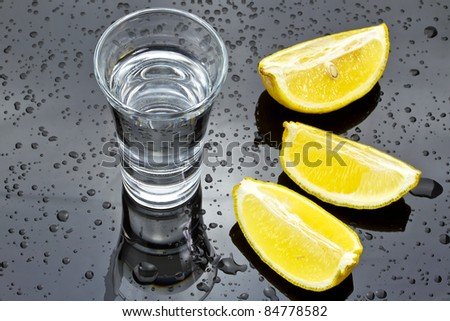 Shot glass of vodka with sliced lemon - stock photo
