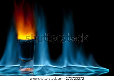 shot glass on fire against black background - stock photo