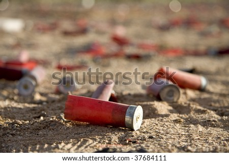 Shot gun shells in the dirt - stock photo
