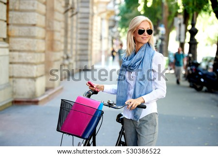 Shot of a beautiful blond woman pushing her bicycle in the city.