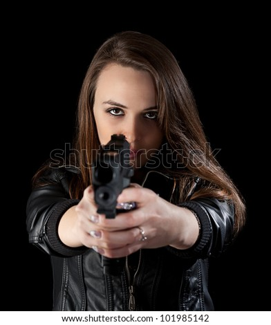Shot of a beautiful girl holding gun, isolated on black background - stock photo