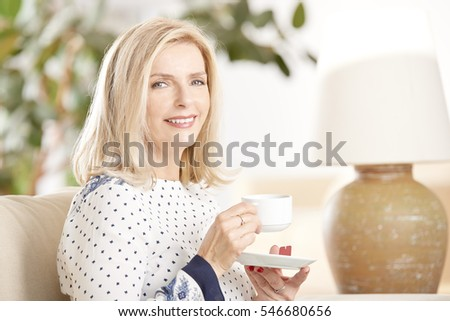 Shot of a beautiful mature woman drinking tea while relaxing at home.