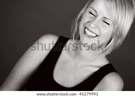 Shot of a Beautiful Smiling Blonde Girl against Dark Background