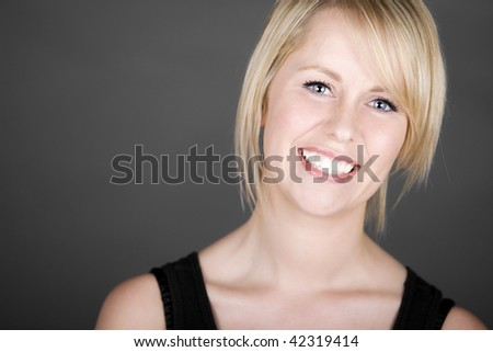 Shot of a Beautiful Smiling Blonde Girl against Grey Background - stock photo