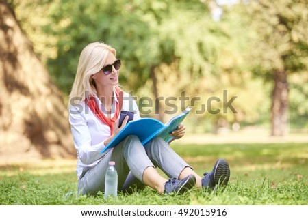 Shot of a businesswoman doing some paperwork while sitting at park before business meeting.