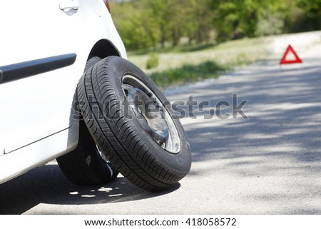 Shot of a car with flat tire problems and a red triangle to warn other road users. - stock photo