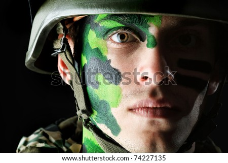 Shot of a conceptual soldier painted in khaki colors. Studio shot over black background.