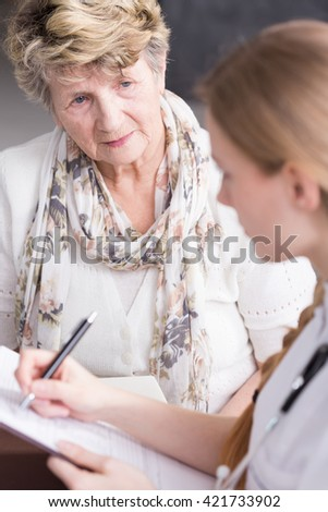 Shot of a concerned elderly woman talking to her nurse - stock photo