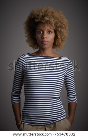 Shot of a confident young afro-american woman standing with folded arms at isolated gray background.