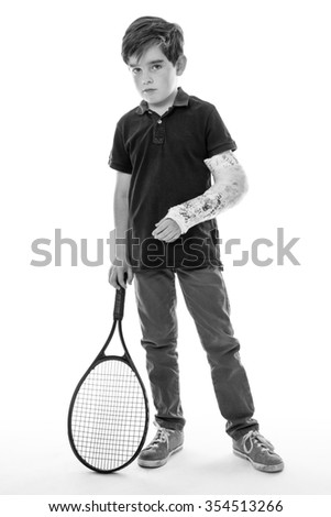 Shot of a cute young boy who has broken his left arm and is unhappy because he can't play tennis - stock photo