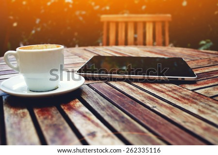 Shot of a digital tablet, smart phone and and coffee mug on a wooden table with empty chair, black touch screen computer on cafe table with coffee cup, flare sun light - stock photo