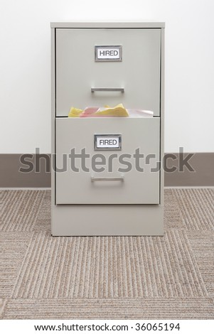 Shot of a filing cabinet with labels reading hired and fired.  The 'fired' drawer is very full.  Vertically framed shot.