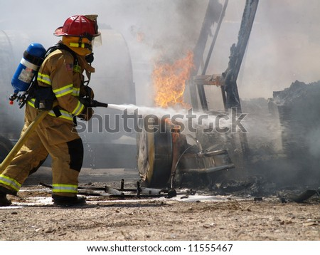 Shot of a firefighter putting out a burning RV. - stock photo