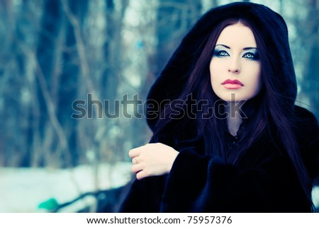 Shot of a gothic woman in a winter park. Fashion. - stock photo
