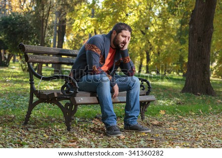 Shot of a grief-stricken man sitting on a park bench with his head in his hands - stock photo