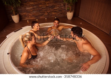Shot of a group of friends drinking champagne and relaxing in jacuzzi. - stock photo