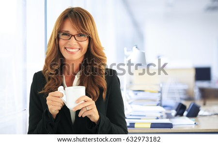 Shot of a happy businesswoman enjoy coffee in the office.