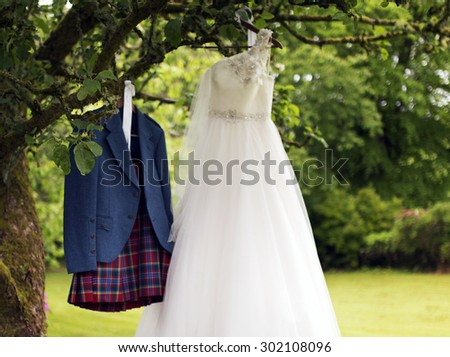 Shot of a Kilt and wedding dress hanging on a tree - stock photo