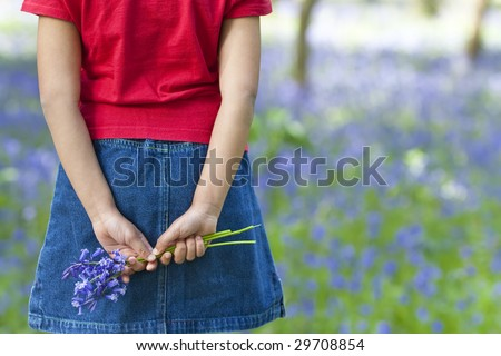 Shot of a little girl holding a bunch of blue bells behind her back, shot against an out of focus background of a bluebell wood.