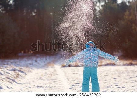 Shot of a little girl throwing a handful of snow up into the air on a sunny winter's day outdoors - stock photo