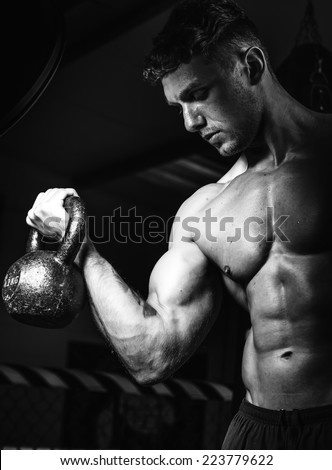 Shot of a male athlete performing dead-lift in a gym - stock photo