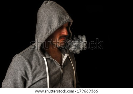 Shot of a man smoking over a black background - stock photo