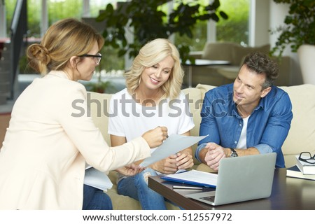Shot of a middle aged couple consulting with real estate agent in their home while sitting on sofa.