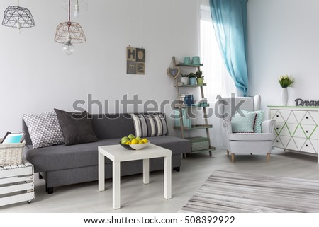 Shot Of A Pastel Living Room With A Grey Sofa And White Coffee Table