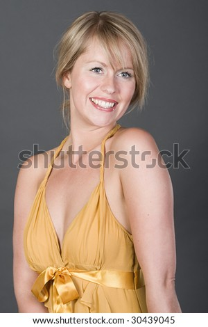 Shot of a Pretty and Happy Blonde in Golden Dress - stock photo