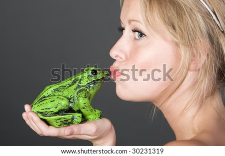 Shot of a Pretty Blonde Girl Kissing a Frog - stock photo