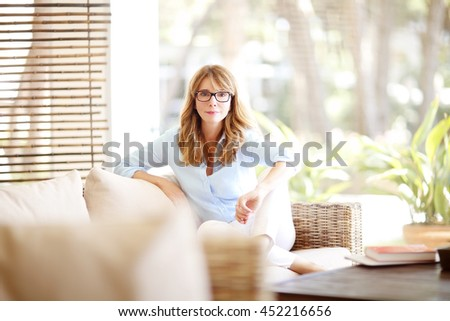 Shot of a pretty middle aged woman relaxing on couch while looking at camera and smiling.