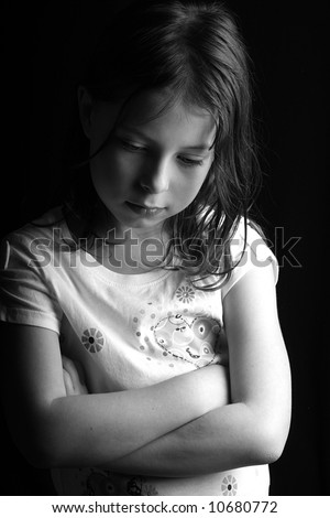 Shot of a pretty seven year old girl looking down with her arms crossed, against a black background - stock photo
