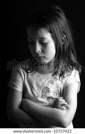 Shot of a pretty seven year old girl looking down with her arms crossed, against a black background II - stock photo