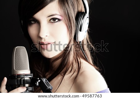 Shot of a pretty young woman in headphones singing a song with a microphone. Shot in a studio. - stock photo