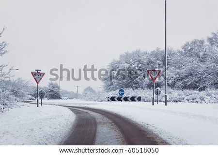 Shot of a road on the approach to a roundabout after a heavy snow fall, Give Way signs - stock photo