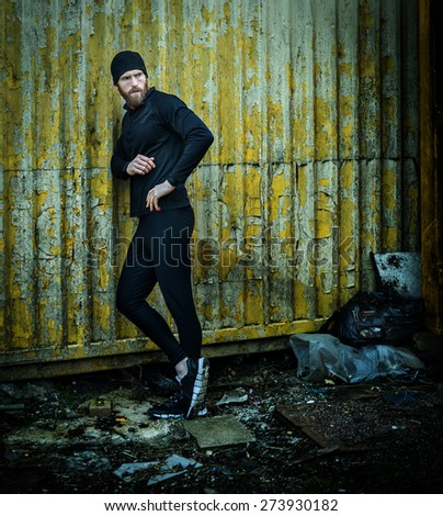 Shot of a runner leaning on garage - stock photo