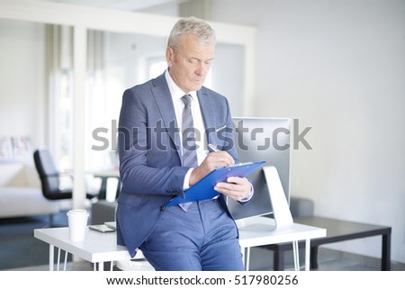 Shot of a senior businessman holding clipboard in his hand and fill the form.