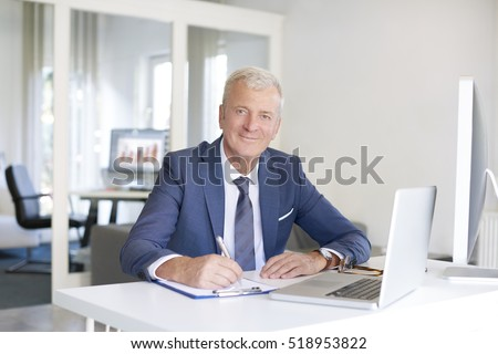 Shot of a senior financial businessman sitting at his workstation in front of computer and laptop while doing some paperwork.