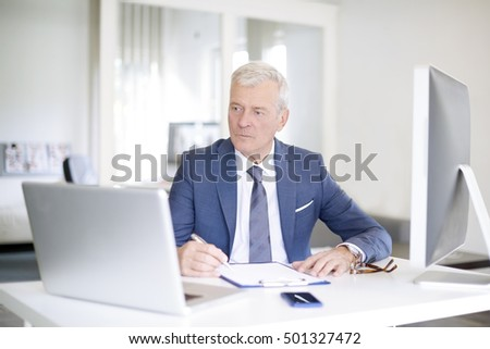 Shot of a senior financial manager sitting at office in front of laptop and and doing some paperwork.