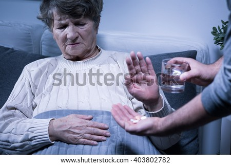 Shot of a senior woman refusing to take her medication - stock photo