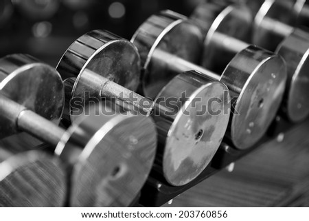 Shot of a set of dumbbells on weight rack with selective focus - stock photo