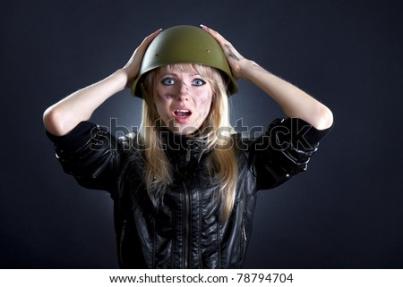Shot of a sexy fashion style attractive woman portrait in military uniform, wearing black leather jacket and dress, posing against black background with make up. - stock photo