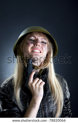 Shot of a sexy fashion style attractive woman portrait in military uniform, wearing black leather jacket holding gun and try to kill her self against black background with make up. - stock photo