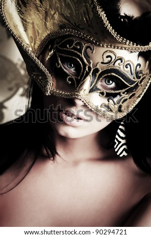 Shot of a sexy woman in a mask over vintage background. - stock photo
